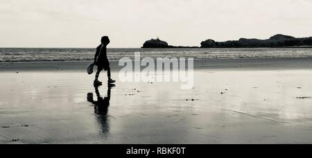 Child walks alone on a beach with reflections in the wet sand in black and white, Cape Hillsborough National Park, Queensland, Australia - Stock Photo