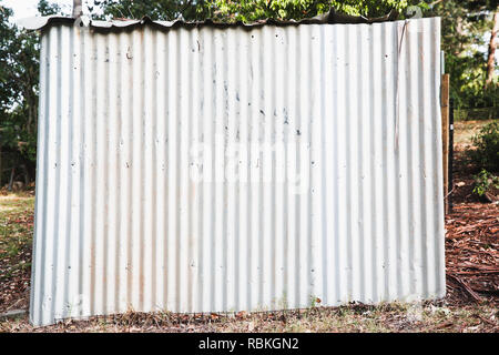 Side of a small rustic, bright looking corrugated iron shed with a shaded back yard scene behind. - Stock Photo