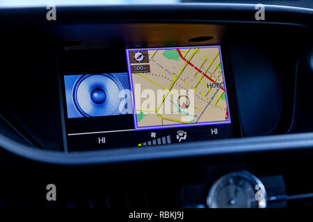 Modern built-in navigator in the car in the panel with the image of the map on the display and voice control paves the route without buttons close-ups - Stock Photo