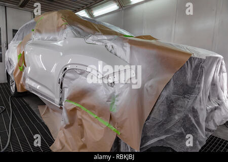 Painting the car with a paint-and-lacquer coating after the damage to the front part of the body is white in the box service center, which are pre-sea - Stock Photo