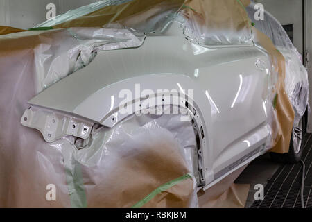 Close-up of the front part of the body of the disassembled car wing after repair and painting white in the workshop, the rest of the crossover frame i - Stock Photo