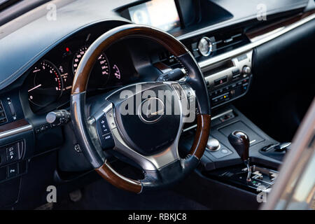 Modern steering wheel with wood elements and metallic chrome parts in the design of an expensive Lexus car on the background of the control panel and