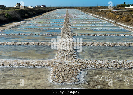 Sea salt production, salt evaporation ponds with crystallized sea salt, Tavira, Algarve, Portugal - Stock Photo