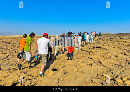 Overtourism, groups of tourists on the way to the Dallol caldera, geothermal field of Dallol, Danakil depression, Afar Triangle, Ethiopia - Stock Photo