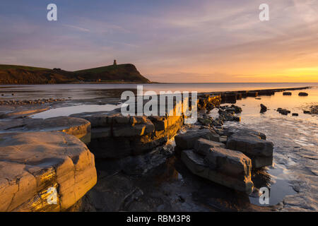 Kimmeridge, Dorset, UK. 11th Jan, 2019. UK Weather. A spectacular winter sunset viewed from the beach and ledges at Kimmeridge Bay on the Dorset Jurassic Coast looking towards Clavell Tower. Picture Credit: Graham Hunt/Alamy Live News - Stock Photo