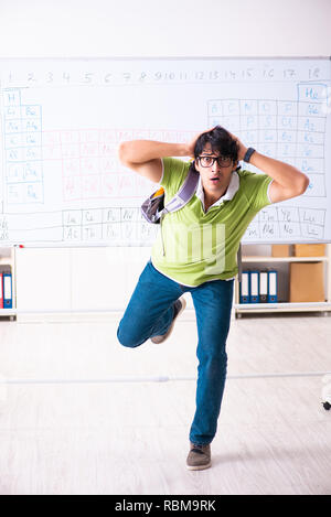 Young male student chemist in front of periodic table - Stock Photo