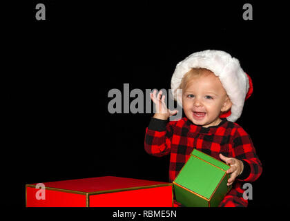 Close up portrait of one one year old baby boy wearing a Santa hat playing with red and green gift boxes, one hand up big smile with teeth showing. Bl - Stock Photo