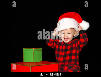 Close up portrait of one one year old baby boy wearing a Santa hat playing with red and green gift boxes, both hands on hat pulling onto head big smil - Stock Photo