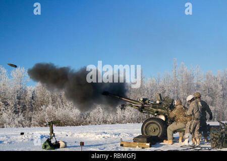 Paratroopers with Alpha Battery, 2nd Battalion, 377th Parachute Field Artillery Regiment, 4th Infantry Brigade Combat Team (Airborne), 25th Infantry Division, fire their M119 Howitzer certifying their capability to shoot accurately in a timely and safe manner Jan. 10, 2019, at Joint Base Elmendorf-Richardson, Alaska. - Stock Photo