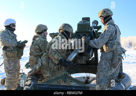 Paratroopers with Alpha Battery, 2nd Battalion, 377th Parachute Field Artillery Regiment, 4th Infantry Brigade Combat Team (Airborne), 25th Infantry Division, load a 105mm, High Explosive, cartridge into their M119 Howitzer during live-fire training at Joint Base Elmendorf-Richardson, Alaska, Jan. 10, 2019. - Stock Photo