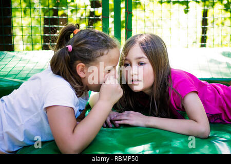 Two girls telling a secret, lying on the trampoline, outdoor in green park. - Stock Photo