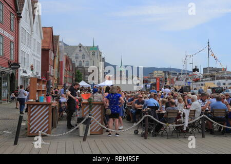 People sit at an outdoor cafe on the UNESCO World Heritage Site, Bryggen, during the traditional Market Day (Torgdagen) in Bergen city, Norway. - Stock Photo