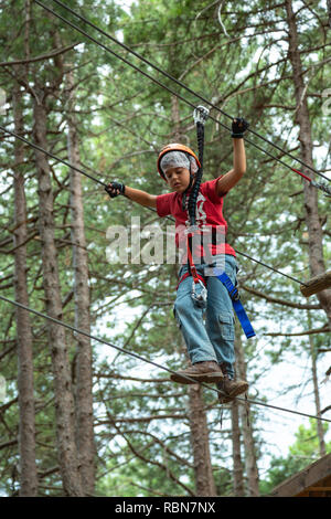 Boy with safety harness climbing  in adventure park in the pine forest. Guardiagrele, .Abruzzo, Italy - Stock Photo