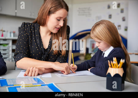 Female primary school teacher sitting at a table in a classroom with a schoolgirl, helping her with her work, selective focus - Stock Photo