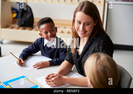 Elevated view of a female primary school teacher sitting between two school kids at table in a classroom, smiling at each other during a lesson - Stock Photo