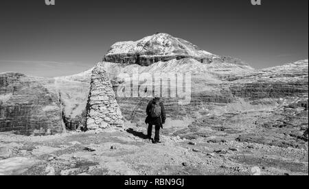 Tourist on the rock of the Sass Pordoi. View towards Piz Boe Mountain, Sella Group, Dolomites, Trentino province, Italy. Image in Black and white - Stock Photo