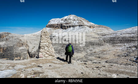 Tourist on the rock of the Sass Pordoi. View towards Piz Boe Mountain, Sella Group, Dolomites, Trentino province, Italy. - Stock Photo