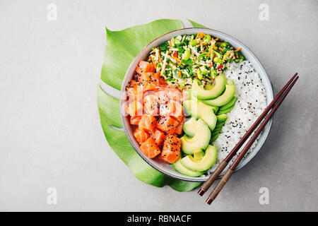 Tasty appetizing poke bowl served with salmon, avocado, rice, salad with edamame. Grey background. View from above with copy space. - Stock Photo