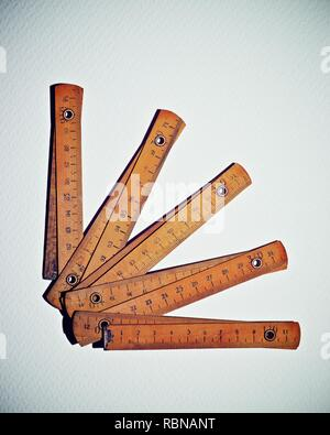Carpenter meter on a white paper. - Stock Photo