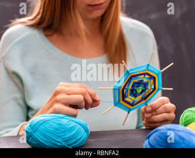 Young girl is doing handmade mandala out of colored yarn. Young woman is taking part in the workshop. - Stock Photo