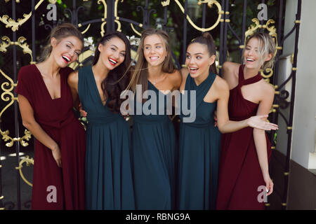 Glamorous girls in the fashion evening dresses posing to make a picture, red, green, having fun, smiling, cheerful, modern, outdoor, make up, party. - Stock Photo