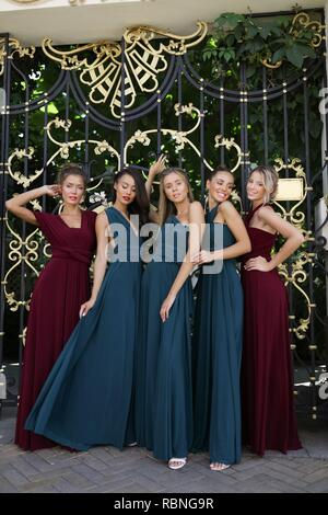 Five bridesmaids in the amazing red and green dresses posing near the gates, party, wedding, having fun, hair style, young, funny, makeup, event, fun - Stock Photo