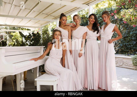 Tender feminine ladies in the light pink dresses standing near the piano, terrace, restaurant , event, party, makeup, hair style, fashion, beauty - Stock Photo
