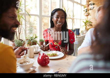Happy young black woman eating brunch with friends at a cafe - Stock Photo