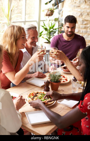 Adult friends eating in a cafe making a toast, vertical - Stock Photo