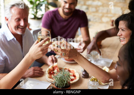 Smiling friends eating at a table in a cafe making a toast - Stock Photo
