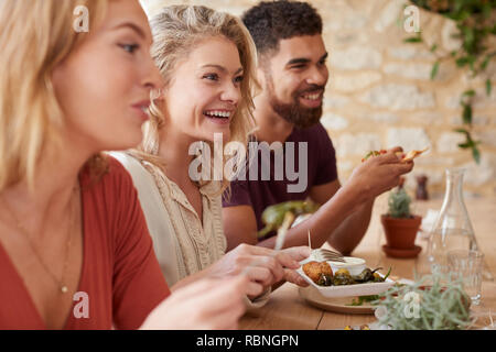 Three young adult friends eating in a restaurant, close up - Stock Photo