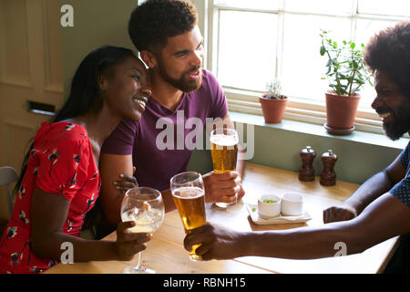 Young couple drinking with an older man in a pub - Stock Photo