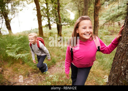 Pre-teen girl taking a break leaning on a tree in a forest, her brother in the background - Stock Photo
