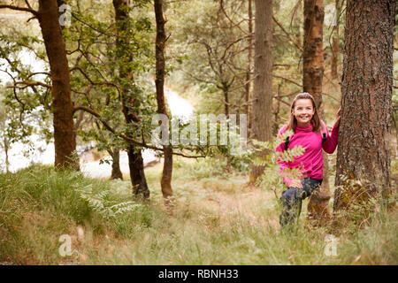 Pre-teen girl stands leaning against a tree in a forest, seen through tall grass - Stock Photo