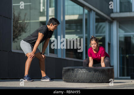 Personal trainer supervising young woman performing a tire flip over - Stock Photo