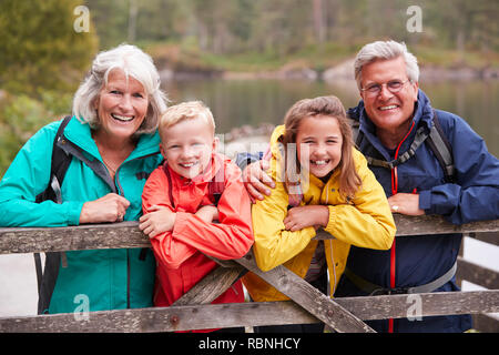 Grandparents and grandchildren leaning on a wooden fence in the countryside laughing, Lake District, UK - Stock Photo