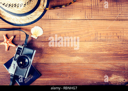 Vintage photo camera, retro hat, sunglasses and seashells border on wooden plank background. Summer holiday design with copyspace. Tropical traveling  - Stock Photo