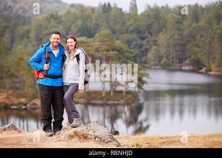 Young adult couple standing on a rock beside a lake in countryside, smiling to camera, full length - Stock Photo