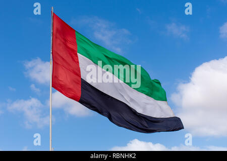 UAE flag blowing in the wind with a blue sky background with clouds in the bright evening sunshine. - Stock Photo