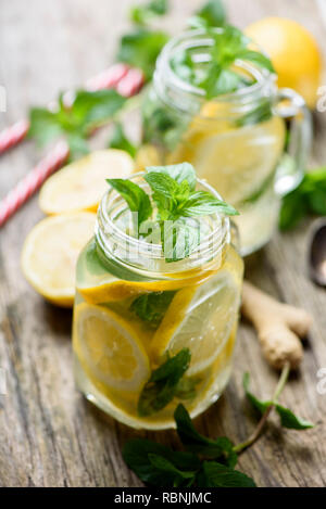 Mint lemonade refreshment beverage in retro mason jars on rustic wooden table. Gignger, lemon and herbs ingredients for summer detox drink recipe. - Stock Photo