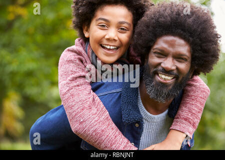 Black man piggybacking his pre-teen son in the park, both smiling to camera, close up - Stock Photo