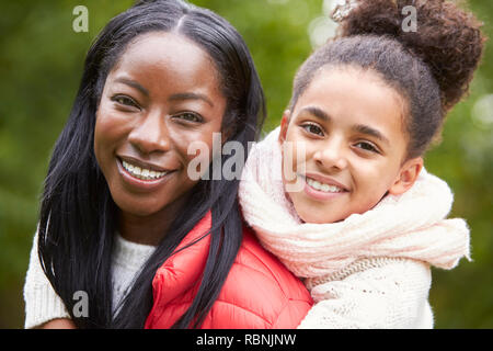 Young black woman piggybacking her pre-teen daughter in the park, both smiling to camera, close up Stock Photo