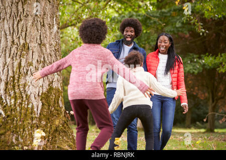 Two kids jumping out from behind a tree to surprise their parents during a walk in the park, back view - Stock Photo