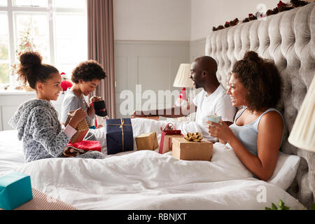 Young kids opening gifts on parents' bed on Christmas morning while their parents sit up in bed watching, side view - Stock Photo