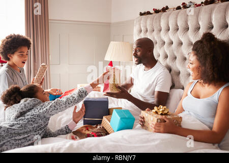 Young mixed race family sitting on parents' bed giving each other gifts on Christmas morning, close up - Stock Photo