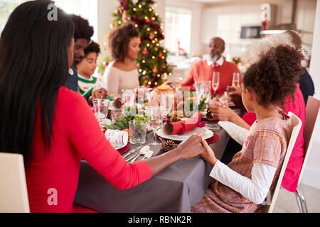 Multi generation, mixed race family holding hands and saying grace at the Christmas dinner table, side view - Stock Photo