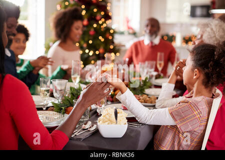 Multi generation mixed race family sitting at Christmas dinner table holding hands and saying grace, selective focus, close up - Stock Photo