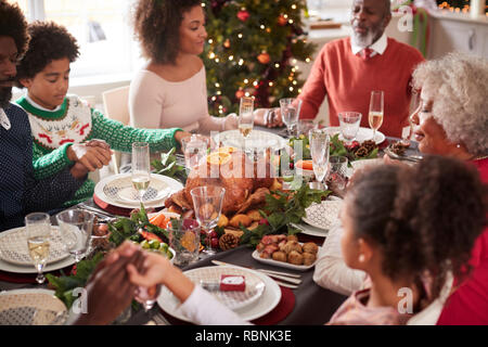 Multi generation mixed race family sitting at Christmas dinner table holding hands and saying grace, elevated view - Stock Photo