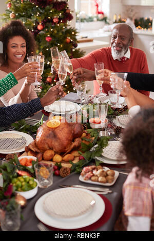 Black grandfather making a toast with his family at the Christmas dinner table, elevated view - Stock Photo