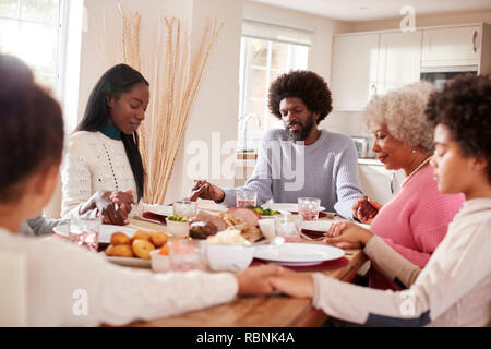 Multi generation mixed race family holding hands and saying grace before eating their Sunday dinner - Stock Photo